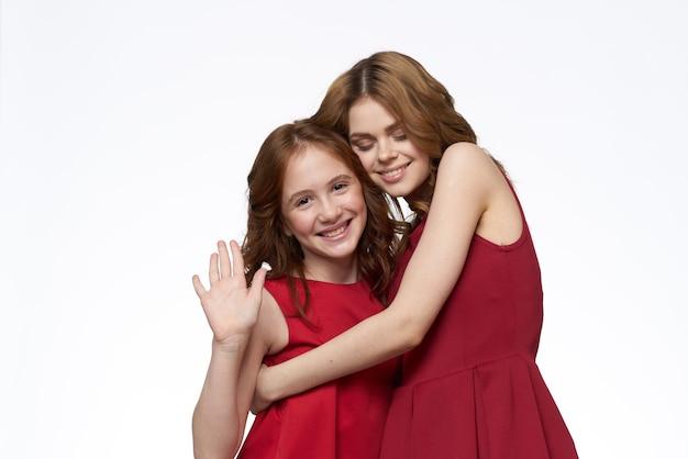 赤いドレスの横にある陽気なママと娘がライフスタイルの明るい笑顔を抱きしめます