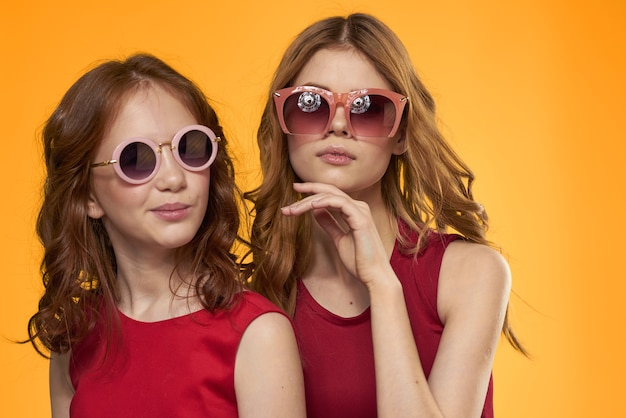 쾌활한 엄마와 딸 선글라스 라이프 스타일 우정 가족 노란색 벽을 입고