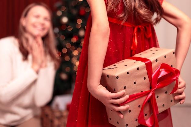쾌활 한 엄마와 그녀의 귀여운 딸 소녀 선물 교환. 행복 한 가족 실내 크리스마스 트리 근처 재미.
