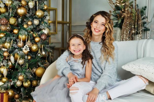 陽気なお母さんと彼女のかわいい娘の女の子は、メリークリスマスと新年あけましておめでとうございますに贈り物を交換します。屋内でクリスマスツリーの近くで楽しんでいる母と小さな子供。部屋にプレゼントを持っている素敵な家族