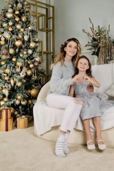 Веселая мама и ее милая дочь девочка обмениваются подарками с рождеством и новым годом. мать и маленький ребенок с удовольствием возле елки в помещении. прекрасная семья с подарками в номере
