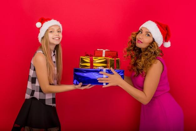 陽気なお母さんとクリスマスプレゼントを持っている彼女のかわいい娘の女の子
