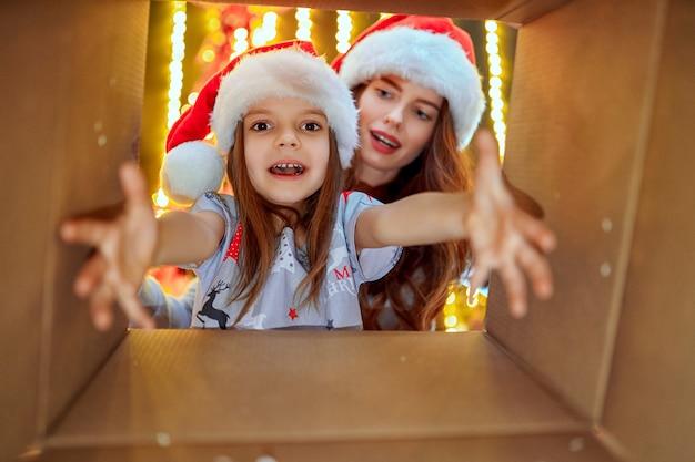 陽気なママと彼女のかわいい娘の女の子がクリスマスプレゼントを開く