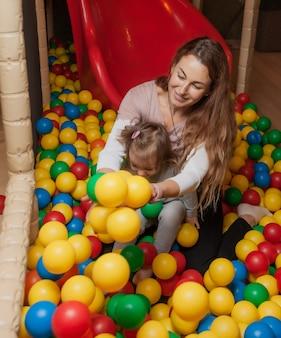 陽気なお母さんと小さな娘が子供向けの娯楽施設の色付きのボールを持ってプールで遊んでいます。家族の休日