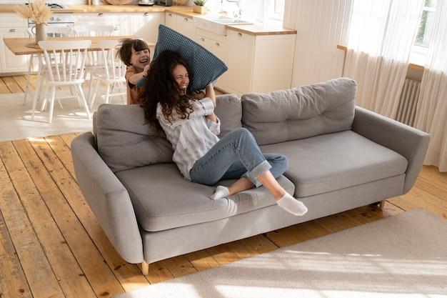 陽気なお母さんと遊び心のある子供が居間で遊んでいる家のソファに座って大喜びの枕投げ