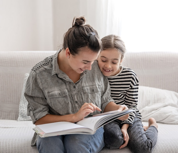 Cheerful mom and daughter are resting at home, reading a book together