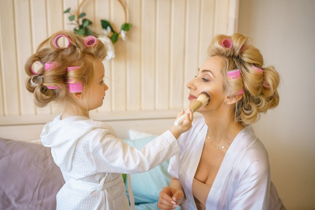 Cheerful mom and daughter on the bed doing makeup