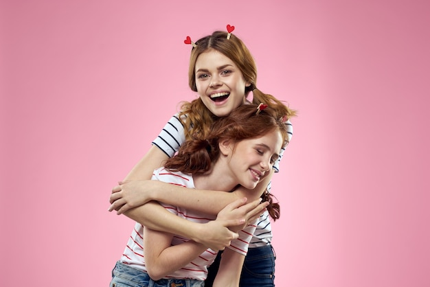 Cheerful mom and daughter on a pink background.