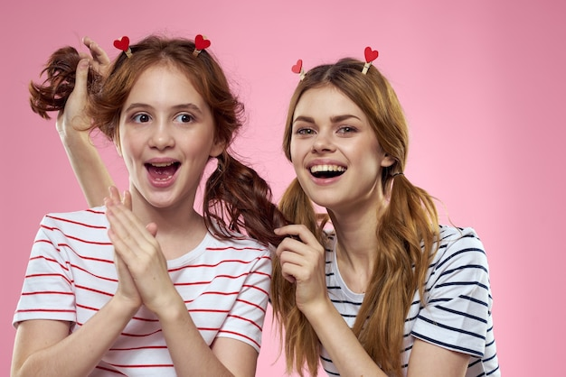 Cheerful mom and daughter wearing striped shirts on pink background.