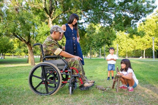 Mamma allegra e papà militare disabile in sedia a rotelle guardando i bambini che organizzano legna da ardere per il fuoco all'aperto. veterano disabili o concetto di famiglia all'aperto