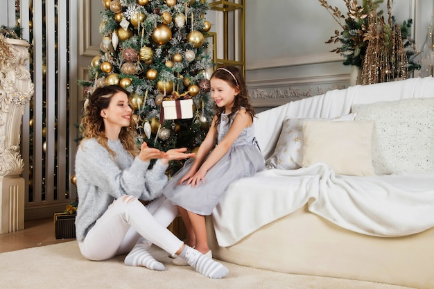 Cheerful mom and her cute daughter girl exchanging gifts on merry christmas and happy new year. mother and little child having fun near christmas tree indoors. lovely family with presents in room