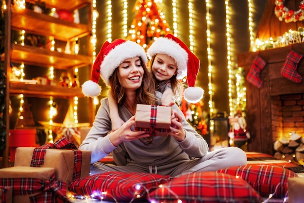 Cheerful mom and her cute daughter girl exchanging gifts. parent and little children having fun near tree indoors. loving family with presents in christmas room.