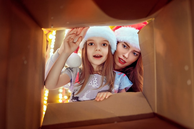 Cheerful mom and her cute daughter girl opening a christmas present