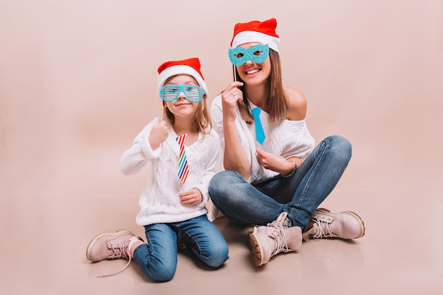 Cheerful mom and her cute happy daughter in carnival masks and santa's hats