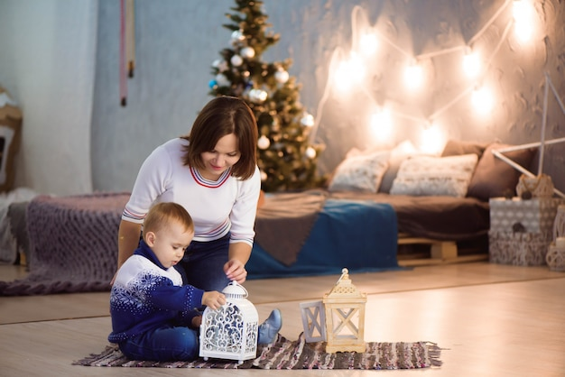 Cheerful mom and her cute son boy having fun near tree indoors. loving family in christmas room.