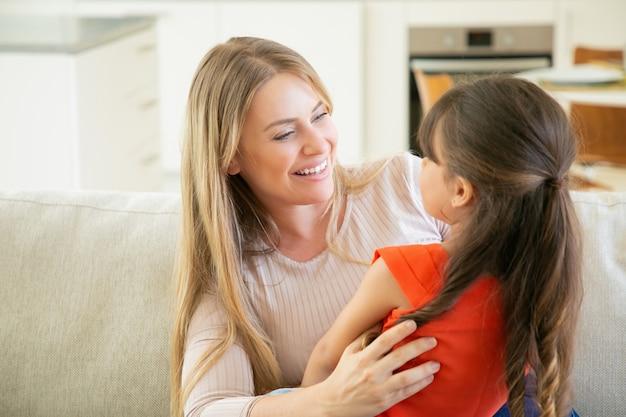 陽気なお母さんが彼女の膝の上で彼女の小さな女の子を腕に抱えて、彼女と話し、笑っています。