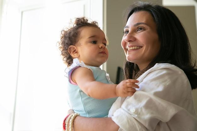 Mamma allegra che tiene dolce figlia tra le braccia. bambina dai capelli ricci carina guardando la madre. genitorialità e concetto di infanzia