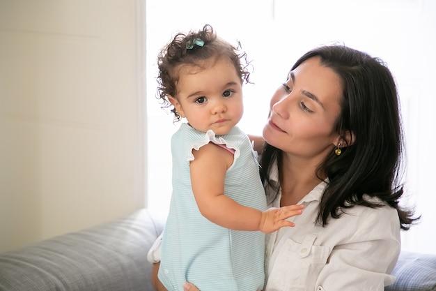 팔에 달콤한 아기 딸을 들고 명랑 엄마입니다. 귀여운 소녀 a. 공간을 복사하십시오. 부모와 어린 시절 개념