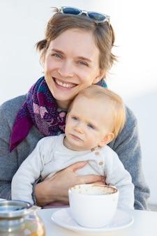 Веселая мама держит на руках сладкого ребенка, попивая кофе в кафе