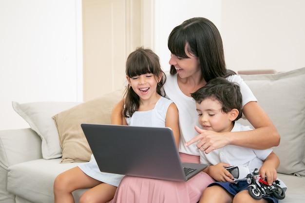 陽気なお母さんが自宅のラップトップで映画やビデオを見て幸せな子供を抱き締めます。