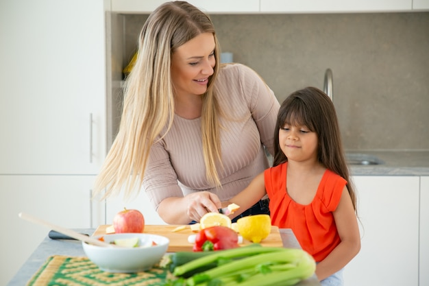 Cheerful mom teaching daughter to cook salad. girl and her mother cutting fresh vegs at kitchen table. family cooking concept