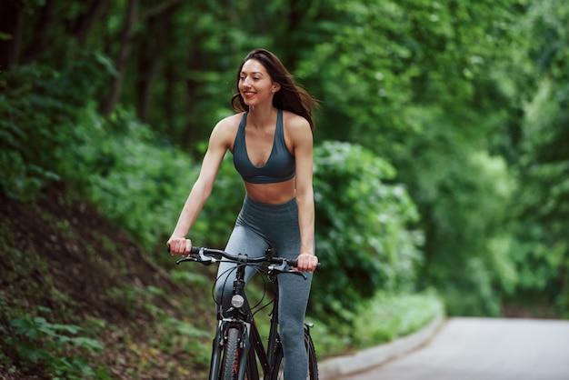 Umore allegro. ciclista femminile su una bici su strada asfaltata nella foresta durante il giorno