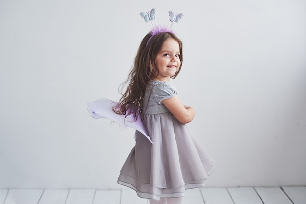Cheerful mood and sincenery smile. lovely little girl in fairy costume standing in room.