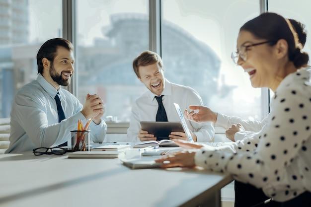 쾌활한 분위기. 회의실의 테이블에 앉아 회의 중에 상사 농담에 웃고있는 경쾌한 젊은 동료