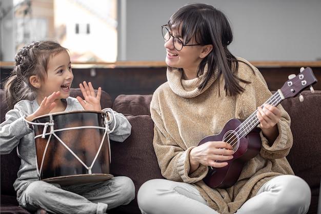 Веселые мама и дочка занимаются музыкальным творчеством, играя дома на диване на барабане и укулеле.