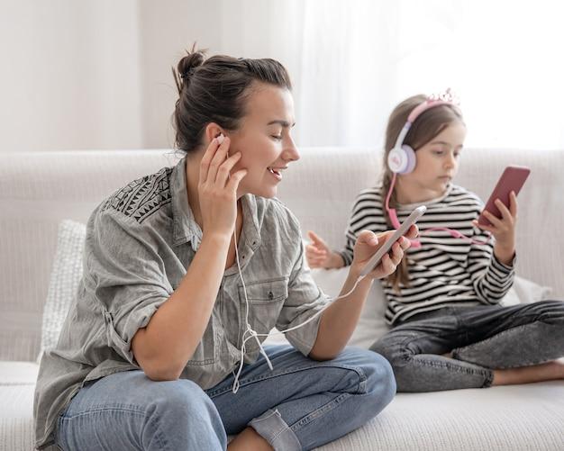Веселая мать и дочь отдыхают дома, слушают музыку в наушниках. концепция счастливой семьи и дружеских отношений.