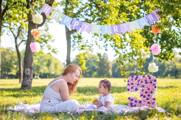 Веселая мать и дочь веселятся в день рождения ребенка на одеяле с бумажными украшениями в парке