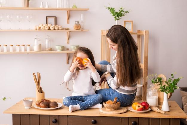 Веселая мать и дочь на кухне готовит завтрак. они едят печенье, играют в блины и смеются.