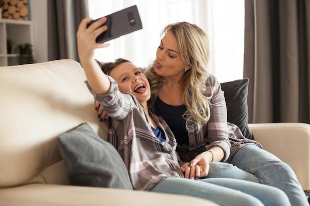 一緒に自分撮りをしているリビングルームのソファに座っている陽気な母と娘。