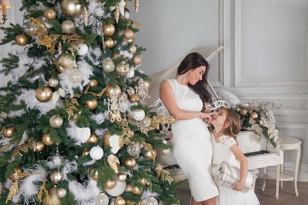 陽気な母親とかわいい娘の女の子と白いピアノと飾られたクリスマスツリー。