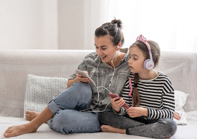Cheerful mother and daughter are resting at home, listening to music on headphones. concept of a happy family and friendly relations.