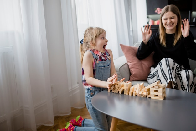 Cheerful mother and daughter playing jenga