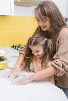 Cheerful mother and daughter putting flour on table