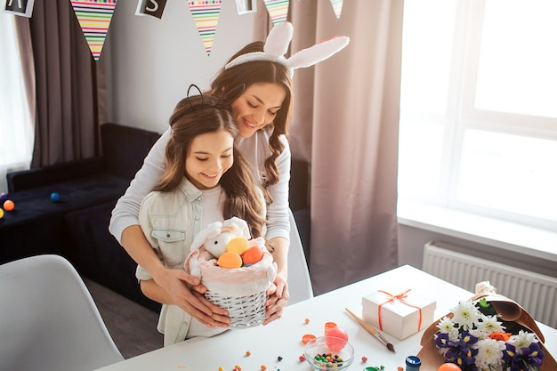 Cheerful mother and daughter stand at table and prepare for easter in room. they hold basket with eggs and sweets together. people wear buny ears on head. daylight.