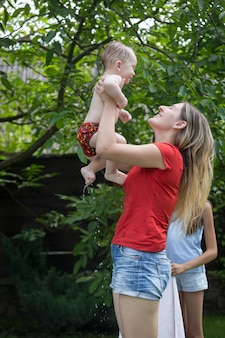Cheerful mother embracing her baby after swimming in pool