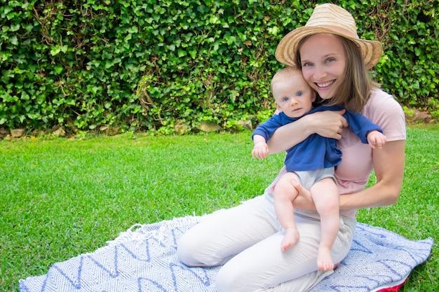 Madre allegra in cappello che si siede sul plaid con neonato sveglio nel parco e che lo tiene. piccolo bambino dai capelli rossi con le gambe nude che guarda l'obbiettivo. vista frontale