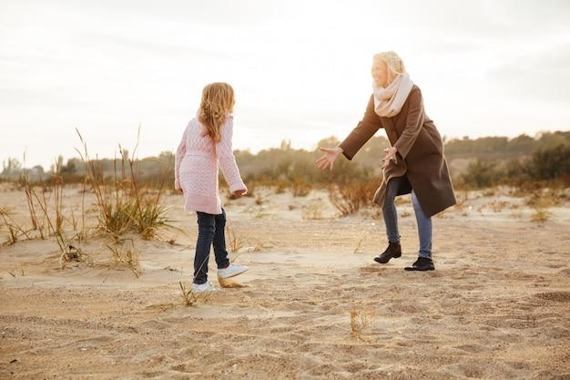 彼女の小さな娘と楽しんで陽気な母