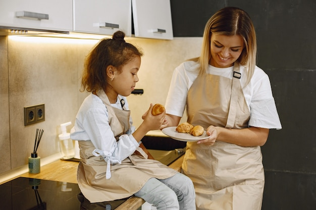 Cheerful mother and little daughter eating fresh baked cookies in kitchen, enjoying homemade pastry, wearing aprons and smiling to each other, having fun at home.
