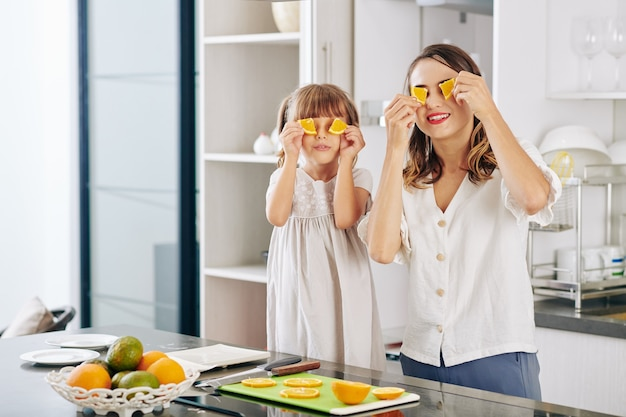 Cheerful mother and little daughter posing with orange slices at kitchen counter