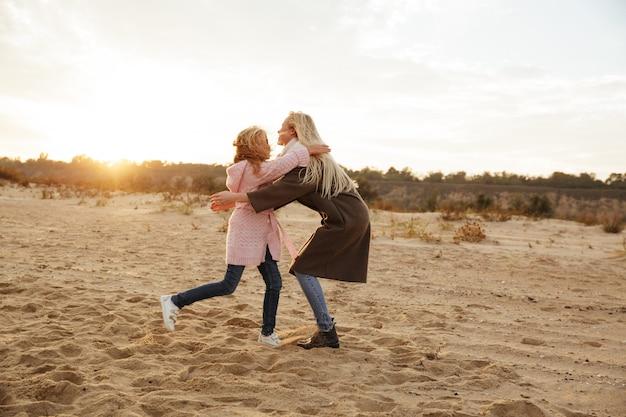 彼女の小さな娘と遊ぶ陽気な母
