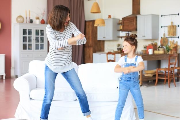 Веселая мать с маленькой дочерью танцует под любимую песню в гостиной дома.