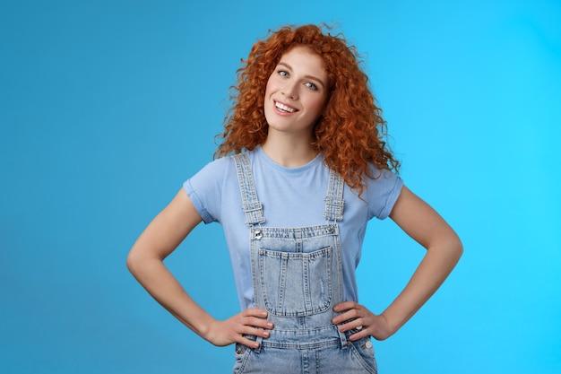陽気なやる気のある達成された魅力的な赤毛の縮れ毛の生姜の女の子は、手を握り、腰に自信を持ってポーズをとる。