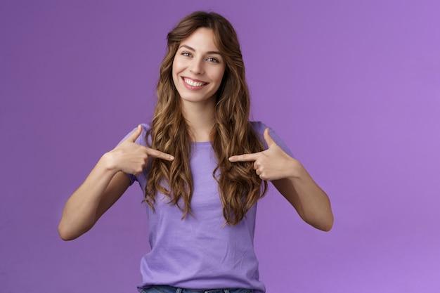 Веселая мотивированная профессиональная напористая кудрявая женщина, указывающая на себя в центре, широко улыбается, предлагает свою помощь, хочет участвовать, хвастливые разговоры о достижениях стоят на фиолетовом фоне.