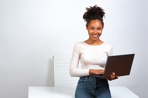 Cheerful mulatto girl have a rest standing in the office holding a laptop