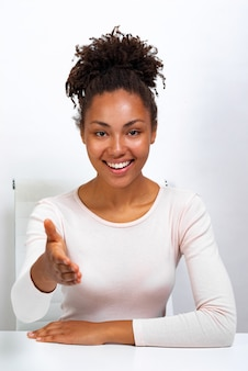 Cheerful mulatto woman straight arm for handshake sitting at the table