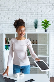 Cheerful mulatto woman takes the tablet in office looking straight.